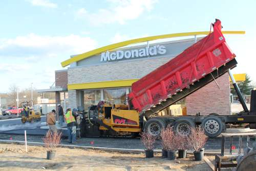 New Construction Paving of a McDonalds. A Dump truck reloads a paver in the foreground